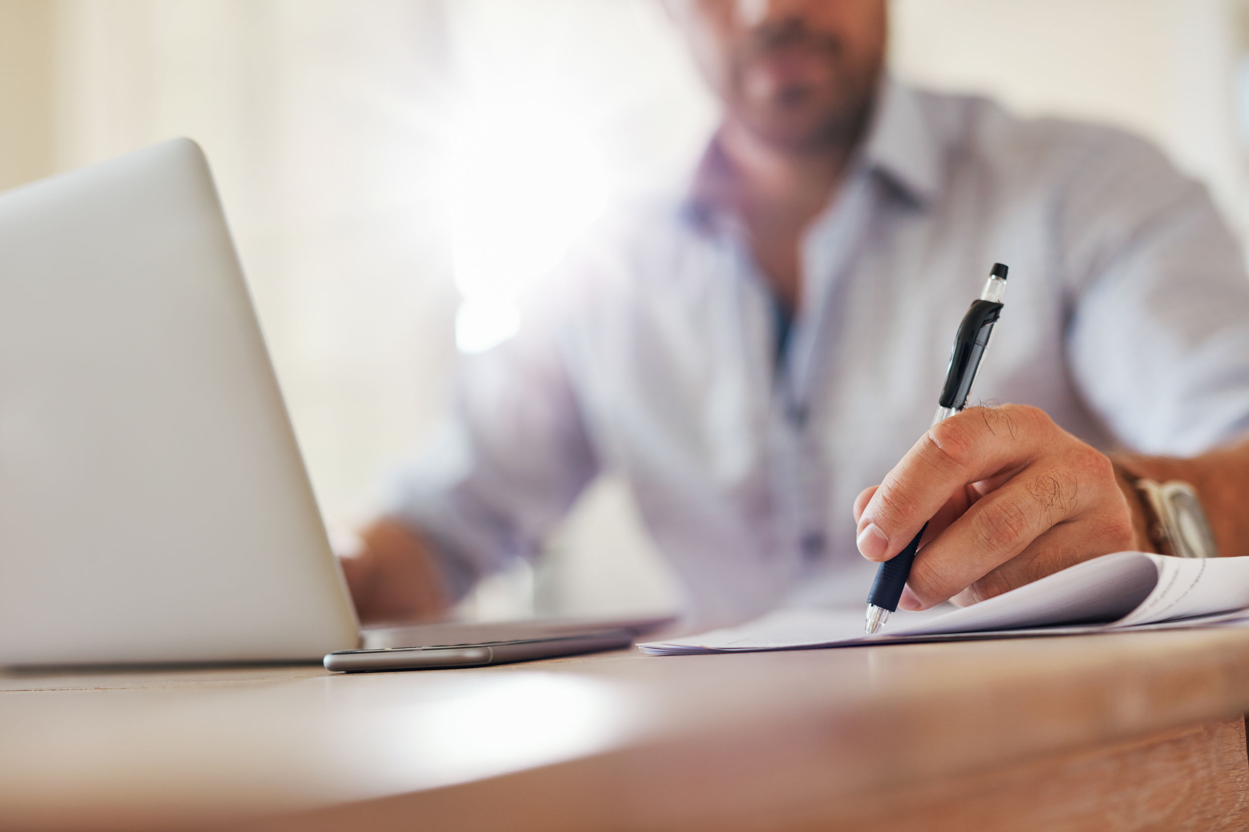 Close up shot of young business man hands with pen writing notes on a paper. Male executive sitting at table at home office.